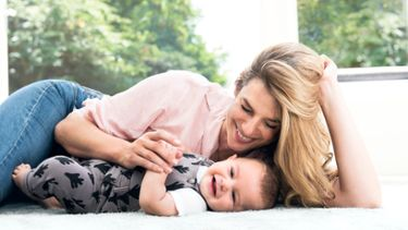 A mum lying on the floor with her baby, smiling and happy, knowing she can breastfeed him without having to remove her PurelanTM 100 lanolin cream.