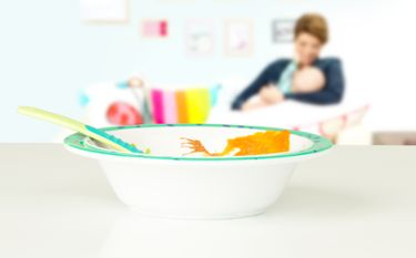 Baby Bowl with food in / Mother and baby in back ground