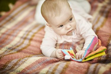 Baby lay on blanket having tummy time holding book
