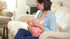 Mother breastfeeding baby sat down